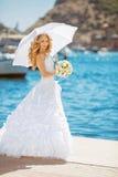 Schöne Braut im Hochzeitskleid mit weißem Regenschirm, draußen p Lizenzfreie Stockfotografie