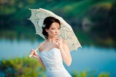 Schöne Braut im Hochzeitskleid mit weißem Regenschirm, draußen Porträt Stockbild