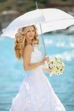 Schöne Braut im Hochzeitskleid mit weißem Regenschirm und Blumenstrauß Lizenzfreie Stockbilder