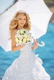 Schöne Braut im Hochzeitskleid mit weißem Regenschirm und Blumenstrauß Stockbilder