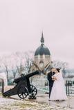 Schöne Braut im langen weißen Kleid und eleganten im Bräutigam, die draußen nahe alter Kanone aufwirft Antike Kirche am Hintergru Lizenzfreie Stockfotografie
