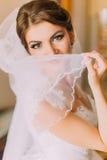 Schöne Braut im weißen Hochzeitskleid, das zuhause mit Schleier aufwirft Weibliches Porträt im Brautkleid für Heirat Stockbilder