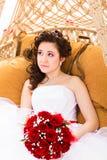 Schöne Braut im weißen Kleid, das rote Rosen des Hochzeitsblumenstraußes hält Stockbilder