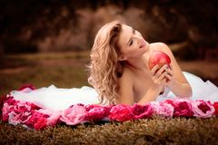 Schöne Braut im weißen Kleid mit den rosa und roten Blumen, Park Stockfoto