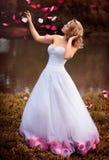 Schöne Braut im weißen Kleid mit den rosa und roten Blumen, Park Lizenzfreies Stockbild