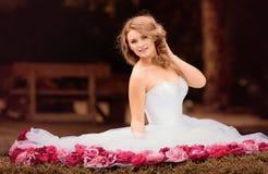 Schöne Braut im weißen Kleid mit den rosa und roten Blumen, Park Lizenzfreie Stockbilder