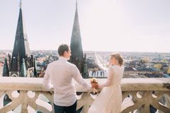 Schöne Braut im weißen Kleid und hübschen im Bräutigam, die zurück auf Balkon mit Ansicht der Stadt steht Lizenzfreie Stockbilder