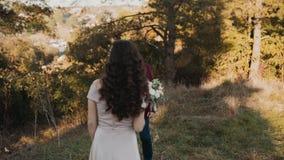 Schöne Braut kommt zu ihrem reizenden Bräutigam im goldenen Park stock footage