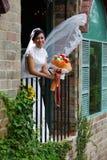 Schöne Braut mit Blumenstrauß auf Terrasse Lizenzfreies Stockfoto