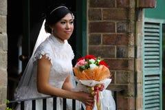 Schöne Braut mit Blumenstrauß auf Terrasse Stockfotografie