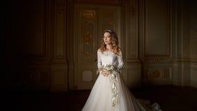 Schöne Braut mit Blumenstrauß im Luxusinnenraum in der barocken Art Stockfoto