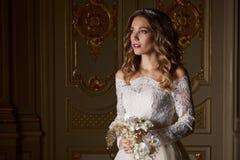 Schöne Braut mit Blumenstrauß im Luxusinnenraum in der barocken Art Stockfotos