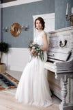 Schöne Braut mit Blumenstrauß nahe dem weißen Klavier Stockfoto