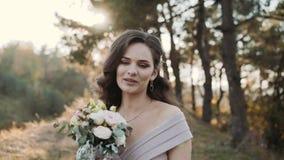 Schöne Braut mit dem Heiratsblumenstrauß, der an der Kamera in einem Park aufwirft stock footage