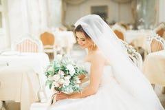 Schöne Braut mit dem Hochzeitsblumenstrauß, der im Hotel aufwirft lizenzfreie stockfotos
