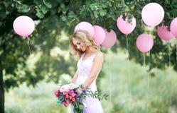 Schöne Braut mit einem Blumenstrauß Stockbild