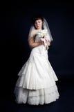 Schöne Braut mit einem Blumenstrauß auf einem schwarzen backgrou Stockbild