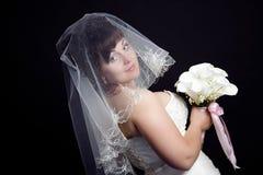 Schöne Braut mit einem Blumenstrauß auf einem schwarzen backgrou Stockfotos