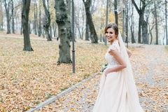 Schöne Braut mit einem Hochzeitsblumenstrauß in ihren Händen draußen in einem Park lizenzfreie stockbilder