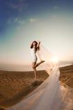 Schöne Braut mit einem langen Schleier auf dem Strand bei Sonnenuntergang Stockfoto
