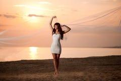 Schöne Braut mit einem langen Schleier auf dem Strand bei Sonnenuntergang Stockbild