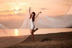 Schöne Braut mit einem langen Schleier auf dem Strand bei Sonnenuntergang Stockfotografie