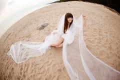 Schöne Braut mit einem langen Schleier auf dem Strand bei Sonnenuntergang Lizenzfreie Stockfotos