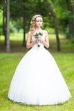 Schöne Braut mit Hochzeitsblumenstrauß von Blumen draußen im grünen Park Stockfotos