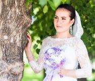 Schöne Braut mit Hochzeitsblumenstrauß von Blumen draußen im grünen Park Stockfoto