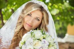 Schöne Braut mit Hochzeitsblumenstrauß von Blumen draußen im gree Lizenzfreies Stockfoto