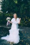 Schöne Braut mit Hochzeitsblumenstrauß von Blumenrosen Stockbilder