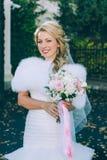 Schöne Braut mit Hochzeitsblumenstrauß von Blumenrosen Stockfotos