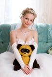 Schöne Braut mit ihrem Tragenspielzeug Stockfotografie