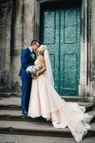 Schöne Braut mit langen Lockengriffen pflegen ` s Hand während eines Wegs lizenzfreies stockfoto
