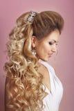 Schöne Braut mit Modehochzeitsfrisur - auf rosa Hintergrund Nahaufnahmeporträt der jungen herrlichen Braut hochzeit Schönes Tanze Stockfotografie