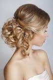 Schöne Braut mit Modehochzeitsfrisur - auf weißem Hintergrund lizenzfreie stockfotografie
