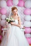 Schöne Braut mit Modehochzeitsfrisur und Hochzeitskleid, das im Studio aufwirft Lizenzfreie Stockfotografie