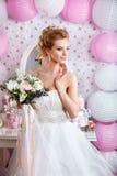 Schöne Braut mit Modehochzeitsfrisur und Hochzeitskleid, das im Studio aufwirft Lizenzfreie Stockfotos