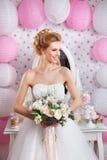 Schöne Braut mit Modehochzeitsfrisur und Hochzeitskleid, das im Studio aufwirft Stockfotos