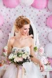 Schöne Braut mit Modehochzeitsfrisur und Hochzeitskleid, das im Studio aufwirft Stockfotografie