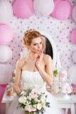 Schöne Braut mit Modehochzeitsfrisur und Hochzeitskleid, das im Studio aufwirft Lizenzfreie Stockbilder