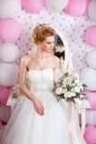 Schöne Braut mit Modehochzeitsfrisur und Hochzeitskleid, das im Studio aufwirft Lizenzfreies Stockfoto