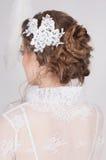 Schöne Braut mit Spitze blüht in ihrem herrlichen dunklen blonden Haar Hohe Hochzeitsfrisur, -borten und -locken Stockfotos