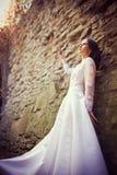 Schöne Braut nahe alter Wand Stockfoto