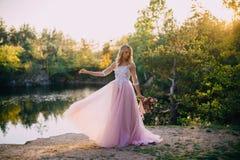 Schöne Braut steht mit einem Blumenstrauß in den Händen auf einem Naturhintergrund Stockfotografie