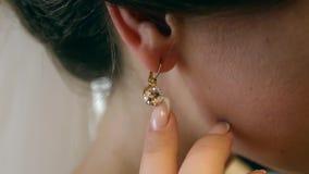 Schöne Braut trägt einen Ohrring im Spiegel stock video