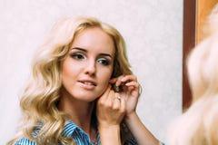 Schöne Braut trägt Ohrringe im Spiegel lizenzfreies stockbild