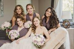 Schöne Braut und Brautjungfern auf Couch lizenzfreies stockfoto
