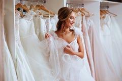 Schöne Braut versucht auf einem eleganten Hochzeitskleid stockbilder