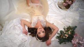 Schöne Braut wird durch Brautkleider, Blick gerade in die Kamera, große schöne Augen umgeben stock video